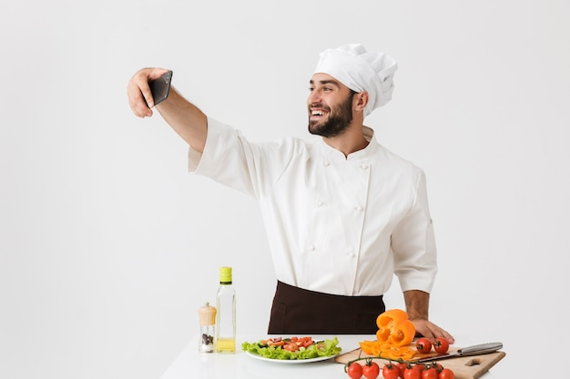 Caucasian cook man in uniform taking selfie photo of vegetable salad on smartphone at work isolated over white wall