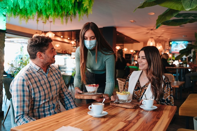 Caucasian couple being served healthy breakfast for diet by a waitress