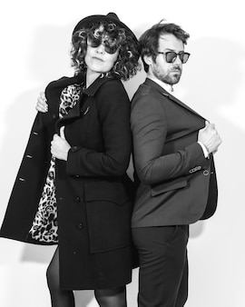 A caucasian couple in a black and white fashion shoot, in elegant suits standing looking at the camera