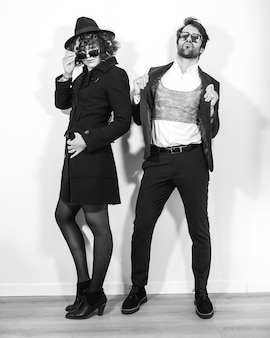 A caucasian couple in a black and white fashion shoot, wearing elegant suits and sunglasses