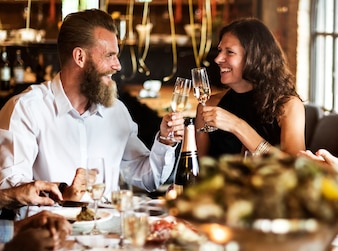 Caucasian couple clinking glasses together at restaurant