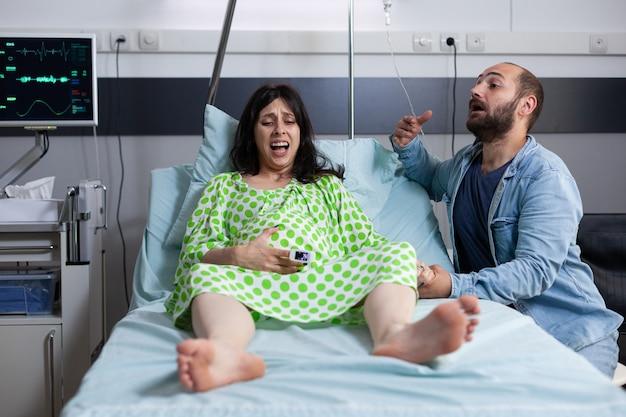 病棟のベッドで赤ちゃんを期待している白人カップル