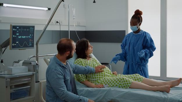 病院の産科病棟で赤ちゃんを期待している白人カップル。アフリカ系アメリカ人の看護師と若い夫と話しているベッドに座っている妊婦。出産のための医療支援