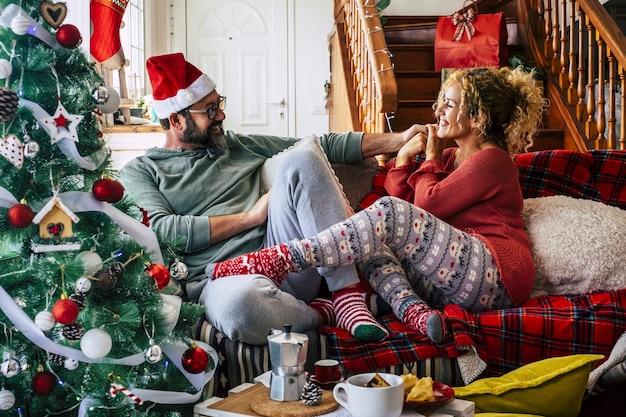 自宅でクリスマスのお祝いの間にリビングルームのソファに座って楽しんでいる白人カップル。装飾されたクリスマスツリーと帽子と靴下のカップル。