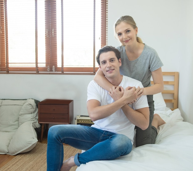 Caucasian couple hug man from back on bed at home