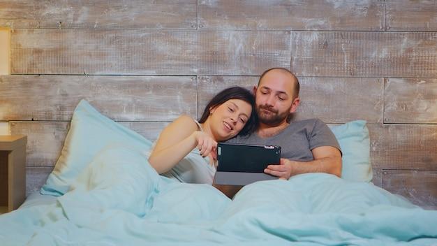 Кавказская пара в пижаме, лежа в постели с помощью планшетного компьютера.