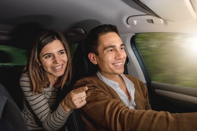 Caucasian couple inside car smiling. woman is pointing something outside with finger while man is driving.