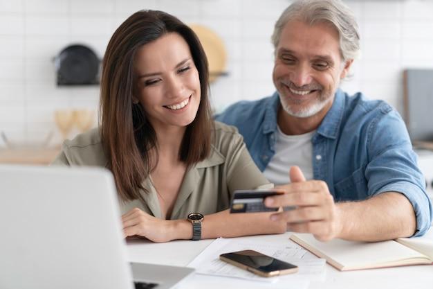 온라인 쇼핑에 관련된 백인 커플, 모바일 애플리케이션에 신용 은행 카드의 결제 정보 입력