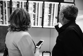 Caucasian couple is checking flight time schedule