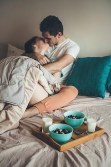 牛乳と一緒にシリアルを食べる前にベッドでキスして抱きしめる白人カップル
