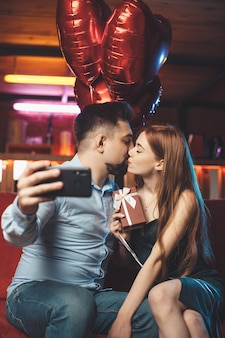 Caucasian couple kissing on a red couch holding air balloons and making a selfie with phone