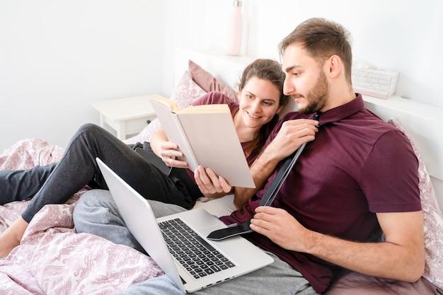 Кавказская пара, лежа в постели и работает из дома. пальма де майорка, испания