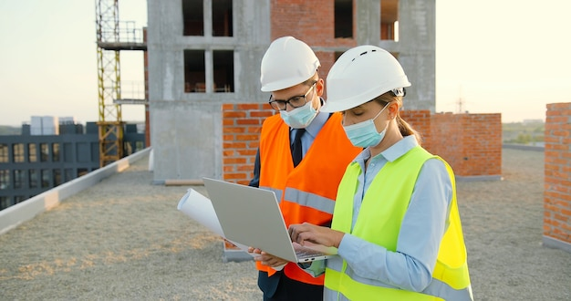 Caucasian couple of male and female constructors in helmets and medical masks talking and discussing plan draft at building side. man and woman builders working at constructing with laptop computer.