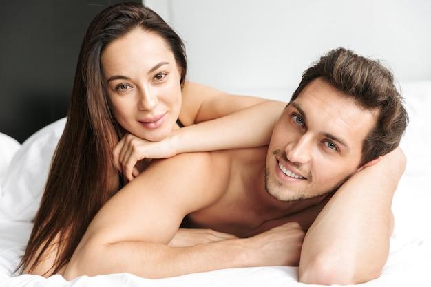 집이나 호텔 아파트에서 침대에 누워있는 동안 백인 부부 남자와 여자가 함께 키스