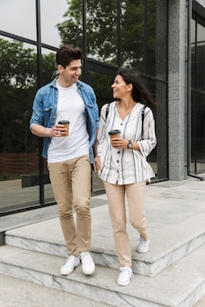 Caucasian couple man and woman in casual clothes drinking takeaway coffee while strolling through city street