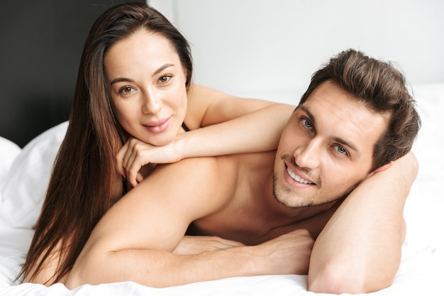Caucasian couple man and woman kissing together, while lying in bed at home or hotel apartment