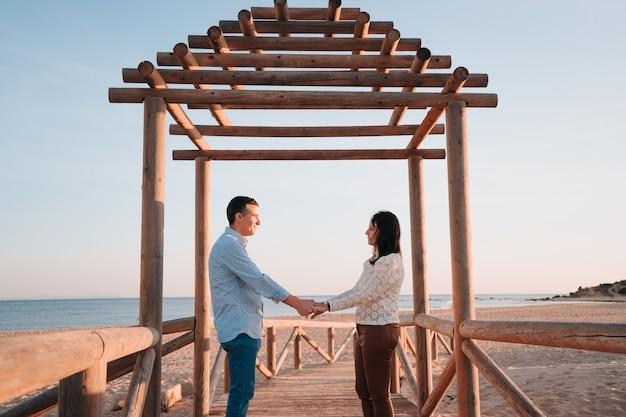 恋に約45年の白人カップルとビーチの木製の桟橋で夕日に手をつないで