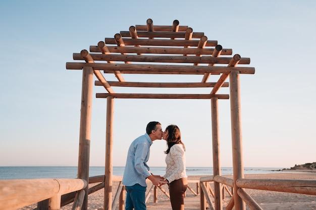 사랑에 약 45 년의 백인 부부와 해변의 목조 부두에서 석양에 키스