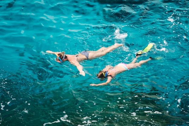 モルディブ島近くのクリスタルターコイズブルーの海でシュノーケリングをする白人カップルの観光客