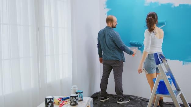 Coppia caucasica pittura parete con pennello a rullo e vernice blu. ristrutturazione dell'appartamento e costruzione della casa durante la ristrutturazione e il miglioramento. riparazione e decorazione.