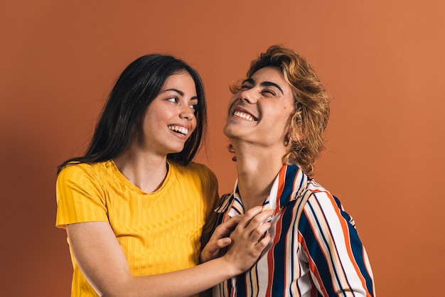 Кавказская пара играет вместе улыбаются перед коричневой стеной