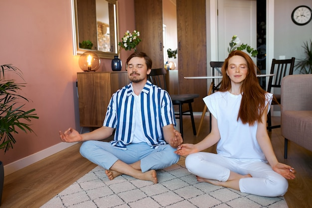 白人カップルは蓮華座で自宅でヨガを練習します