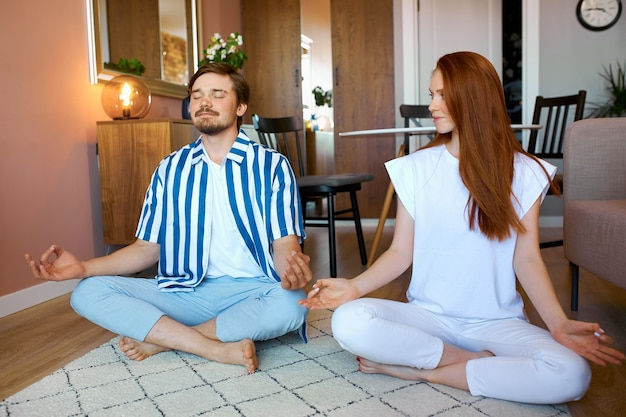 Caucasian couple practice yoga at home in lotus pose