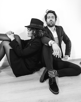 A caucasian couple sitting on the floor in a black and white fashion shoot, in elegant suits and with serious looks.