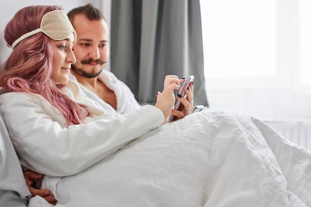 一緒にベッドに横たわっているスマートフォンを使用して、朝にソーシャルネットワークのニュースをチェックし、時間をリラックスする白人カップル