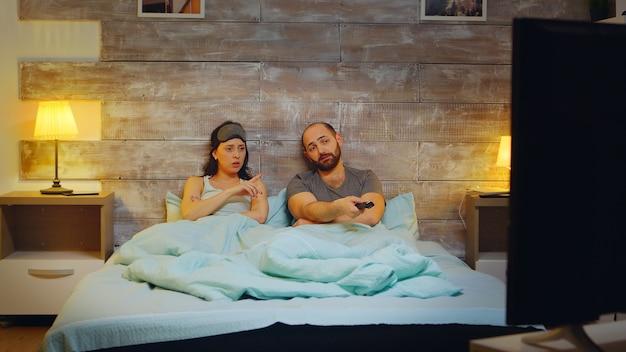 夜にテレビのリモコンを使用している白人のカップル。睡眠マスクを持つ女性。