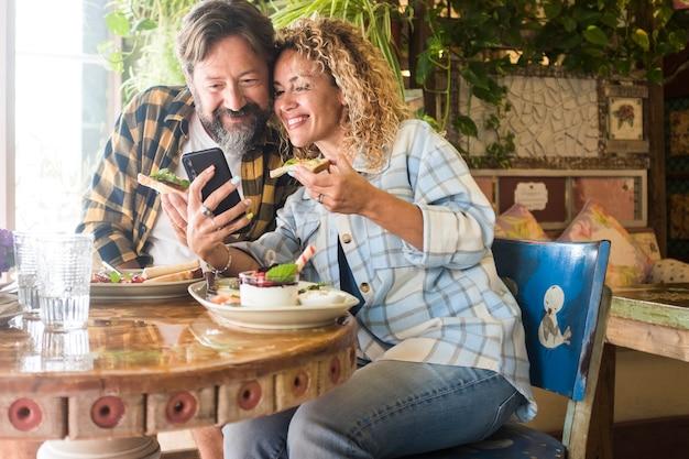 レストランで昼食をとりながら携帯電話を使用してメディアコンテンツを見ている白人カップル。カフェで食事をしたり、ソーシャルメディアコンテンツを共有したりしながら楽しんでいるカップル