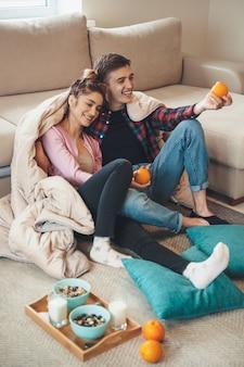Кавказская пара со здоровыми привычками ест хлопья с молоком и апельсинами, сидя на полу с одеялом и подушками