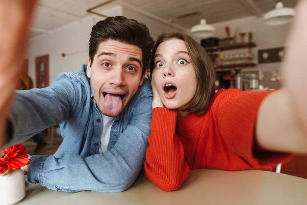 Caucasian couple woman and man having fun together and playing around, while taking selfie in cafe