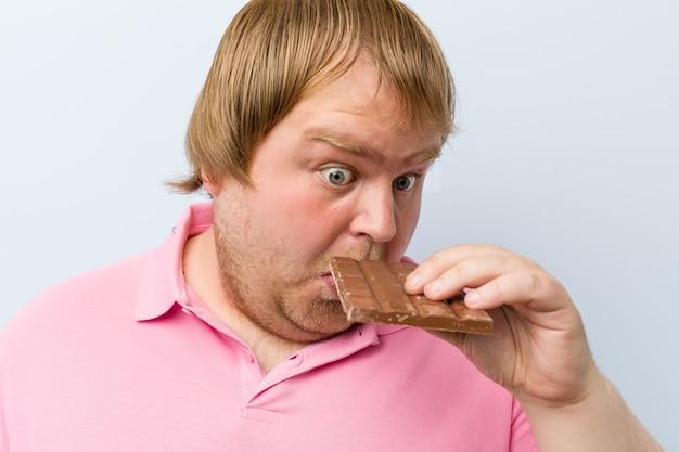 Кавказский сумасшедший блондин толстый мужчина держит шоколадную таблетку
