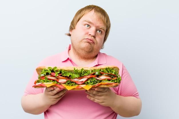 Кавказский сумасшедший блондин толстый мужчина держит гигантский бутерброд