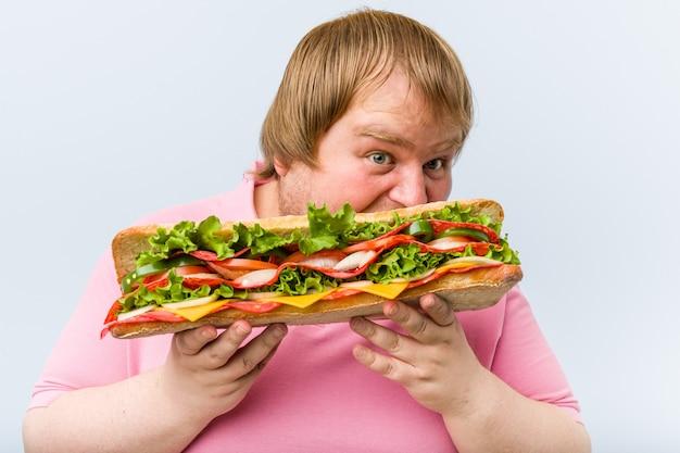 巨大なサンドイッチを保持している白人のクレイジーブロンドデブ男