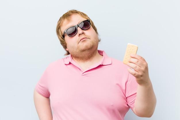 アイスクリームを保持している白人の狂気の金髪デブ男