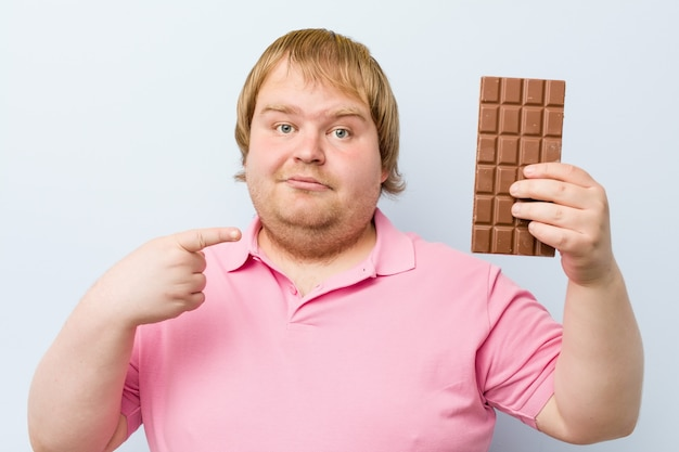 Caucasian crazy blond fat man holding a chocolate tablet