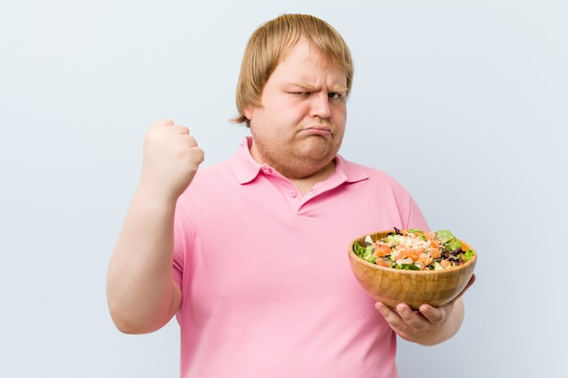 Caucasian crazy blond fat man holding a salad bowl
