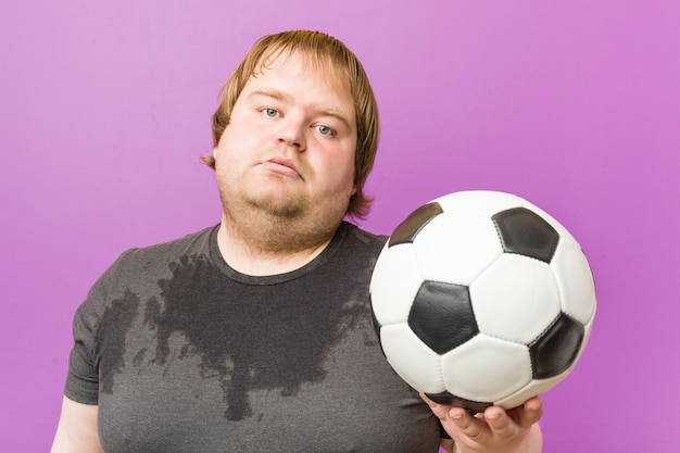 Caucasian crazy blond fat man playing football