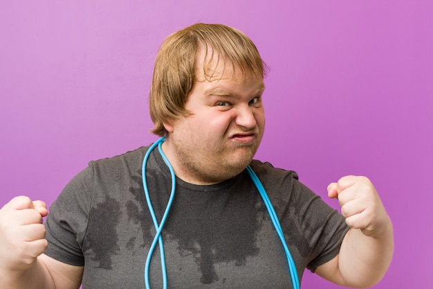 Caucasian crazy blond fat man sweating with a jump rope