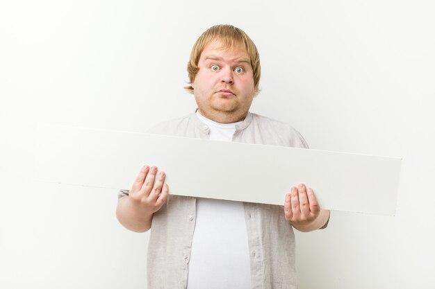 プラカードを持つ白人の狂った金髪の太った男
