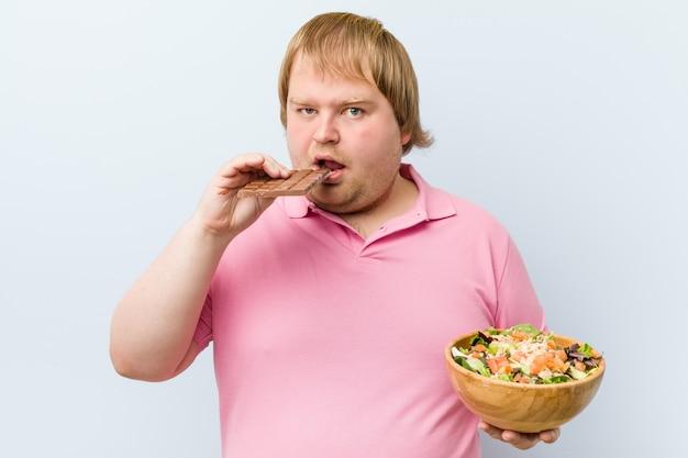 Caucasian crazy blond man choosing between chocolate tablet or salad bowl