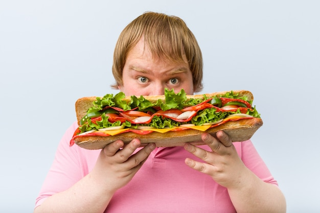 巨大なサンドイッチを保持している白人の狂気の金髪男