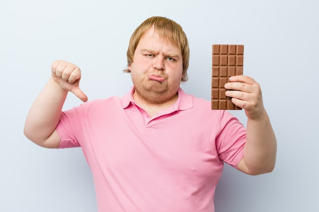 Caucasian crazy blond man holding a chocolate tablet
