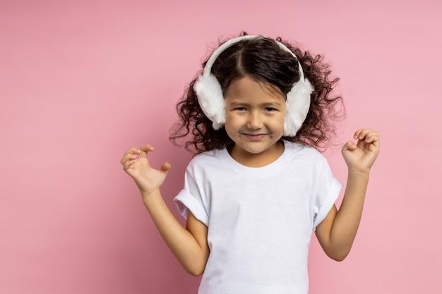 Кавказская кудрявая маленькая девочка, одетая в белую футболку, притворяется кошкой, играя с друзьями, поднимает руки и делает жест когтями, как животное, корчит рожи.