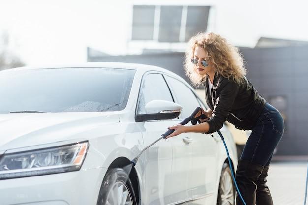 白人の巻き毛の女性が洗車で車を掃除する