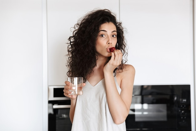 Caucasian curly woman with long dark hair wearing silk leisure clothing holding glass of water, and eating strawberry in flat