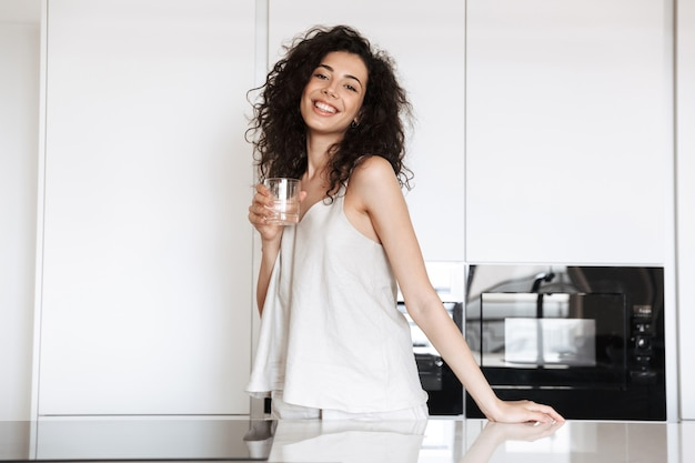 Caucasian curly woman with long dark hair wearing silk leisure clothing smiling and holding glass of water, while standing in flat kitchen