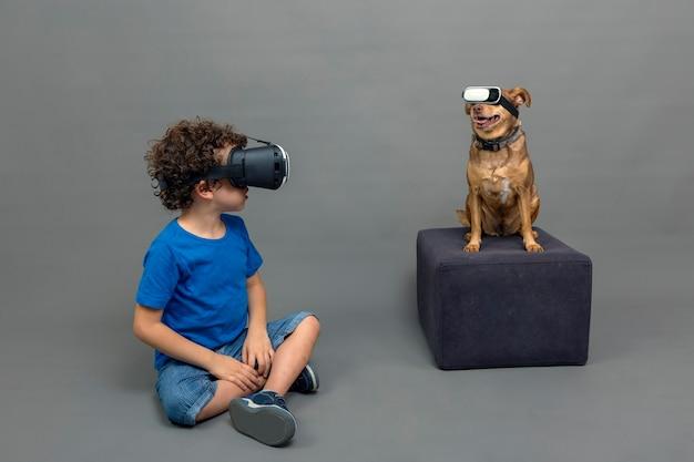 Кавказский кудрявый мальчик и его щенок в очках виртуальной реальности на сером фоне